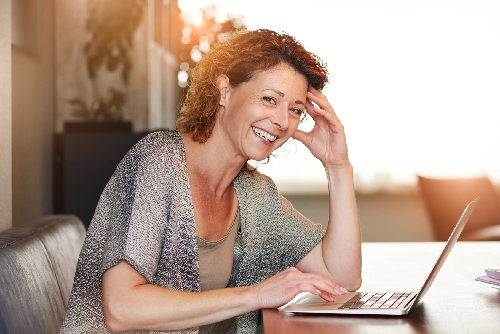 Woman sitting at table with smiling  with laptop