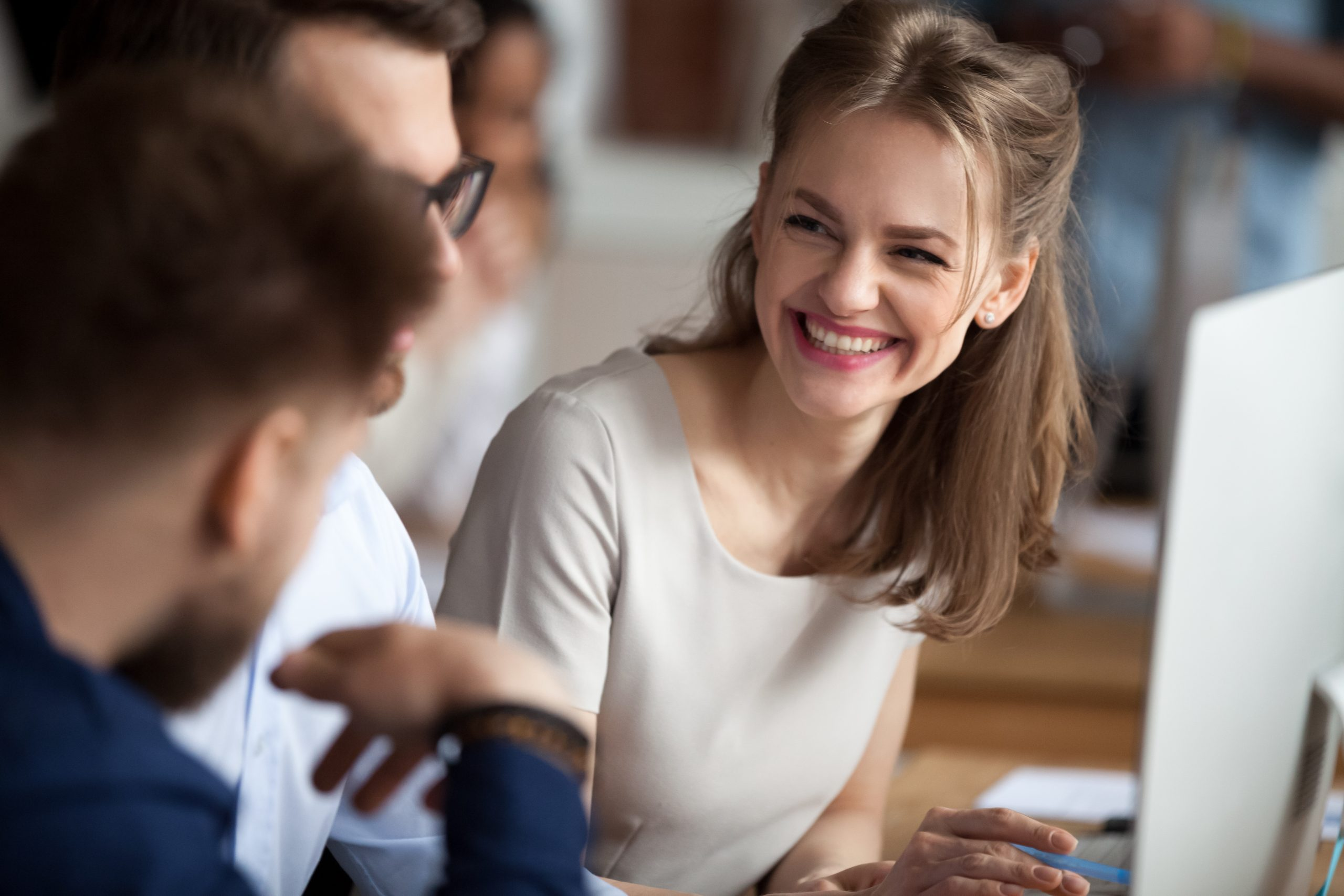 Smiling young woman talking with colleagues at shared workplace