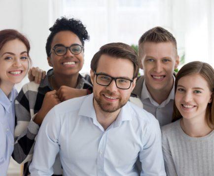 Portrait of smiling diverse millennial team posing together
