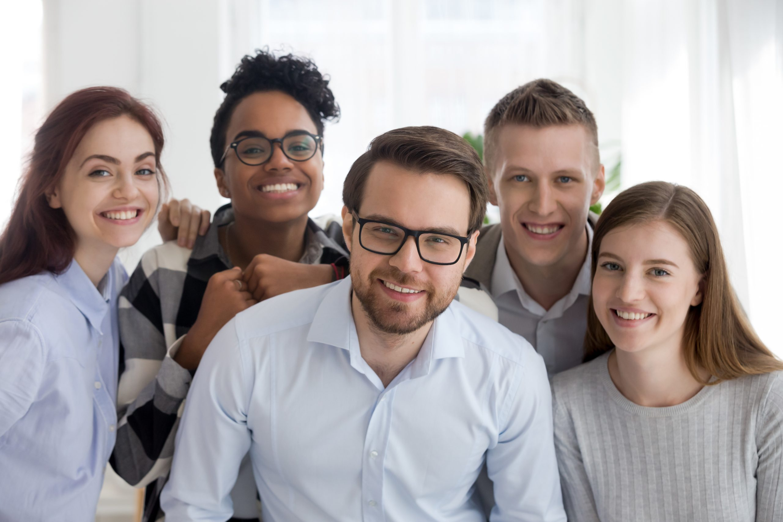 Portrait of smiling diverse millennial team posing together